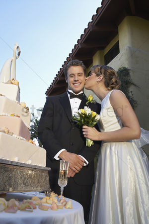 Kissing : Bride kissing groom near wedding cake portrait