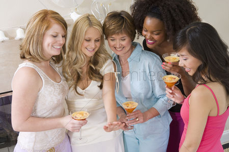 Celebrating : Bride standing together with friends watching her engagement ring