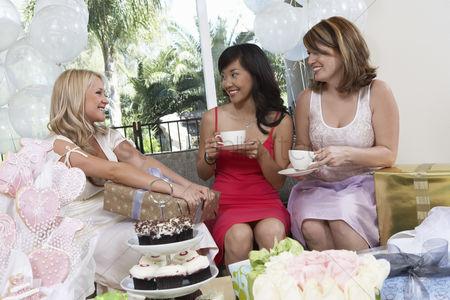 Celebrating : Bride talking to friends giving gifts at bridal shower