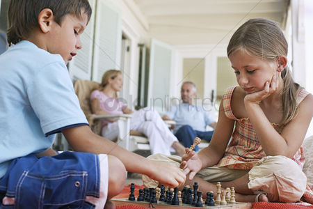 Children playing : Brother and sister  7-9  playing chess on porch parents in background