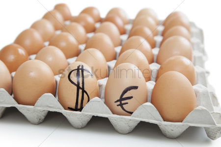 Egg tray : Brown eggs in carton with dollar and euro sign over white background