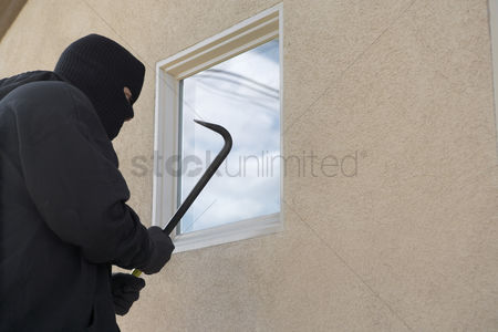 Thief : Burglar using crowbar to break into house
