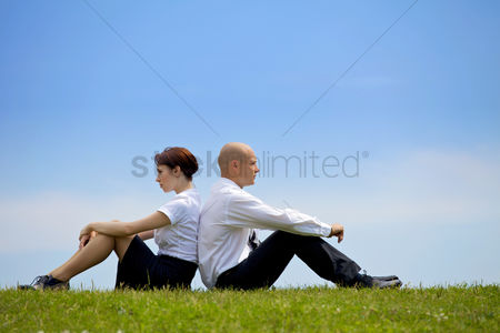 Bald : Business couple sitting back to back on grass