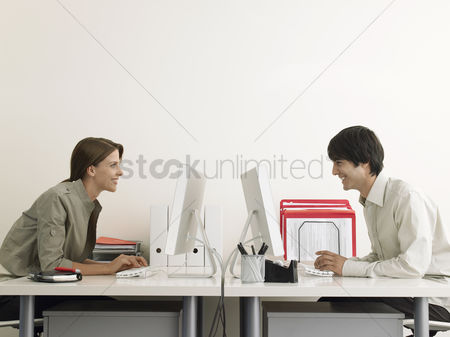 Interior background : Business man and woman working on computers face to face