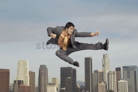 Arts : Business man doing martial arts mid-air above city