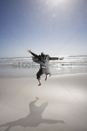 Bald : Business man jumping mid air on beach back view