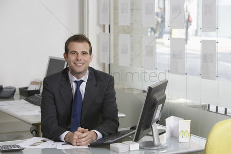 Business suit : Business man sitting at desk in office portrait