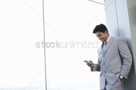 Business suit : Business man using cell phone smiling