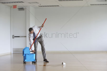One man only : Business man using mop in empty room