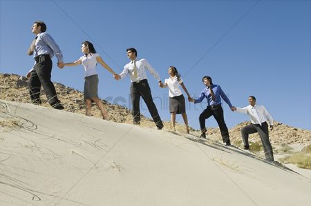 Business suit : Business people holding hands while walking uphill in the desert