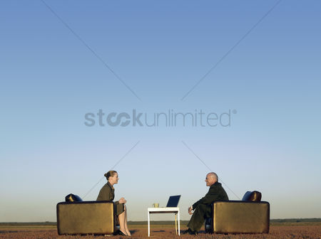 People : Business people sitting in chairs on open plain
