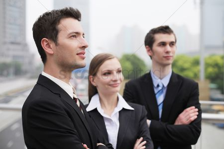 Motivation business : Business people standing outdoors with arms crossed