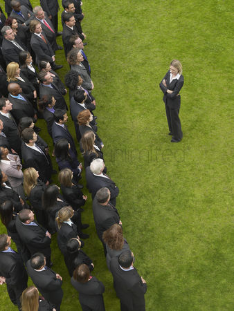Selection : Business woman facing large group of business people in formation elevated view