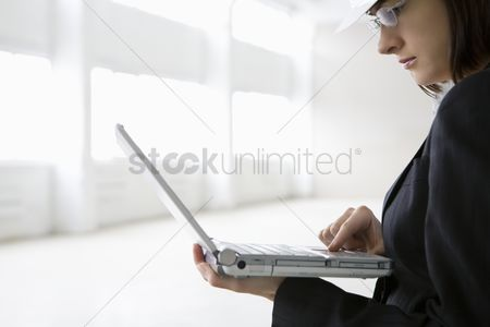 Jacket : Business woman working on laptop in empty warehouse