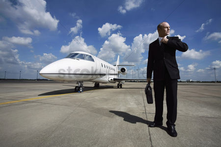 Transportation : Businessman adjusting his tie on runway with private jet in the background