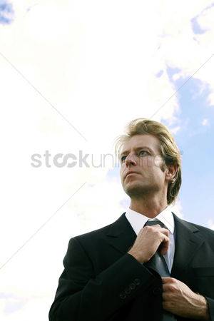 Man suit fashion : Businessman adjusting his tie while looking away
