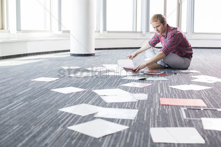 Creativity : Businessman analyzing photographs while sitting on floor at creative office