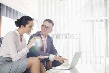 Showing : Businessman and businesswoman discussing over laptop in office