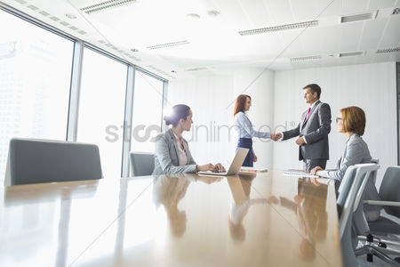 Businesswomen : Businessman and businesswoman shaking hands in conference room