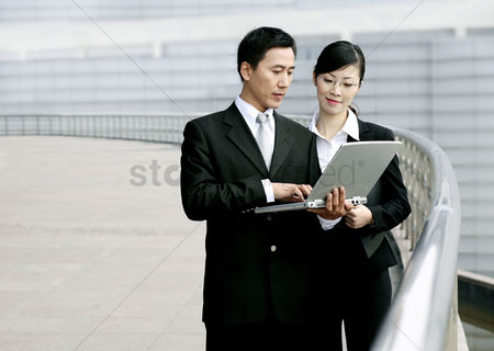 Outdoor : Businessman and businesswoman sharing a laptop