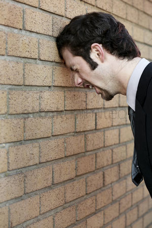 Business suit : Businessman banging his head against the wall