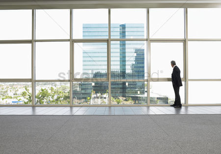 Contemplation : Businessman by window in office building