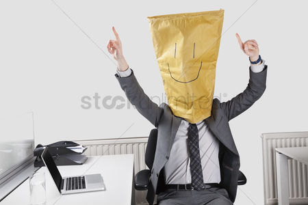 Office worker : Businessman cheering with smiley drawn on paper bag over face in office