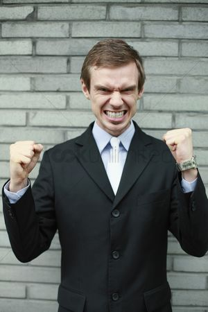 Mad : Businessman clenching teeth and showing fists