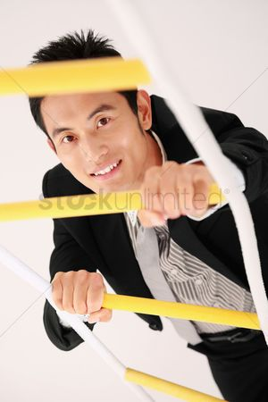 Motivation business : Businessman climbing up rope ladder