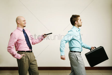 Bald : Businessman controlling his colleague with a remote control