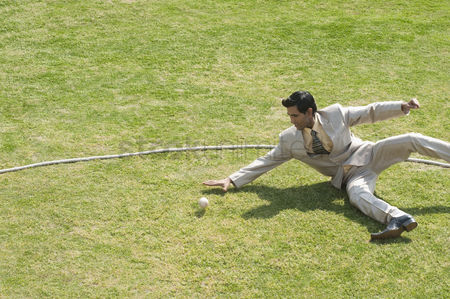 Diving : Businessman diving to stop a ball near boundary line in a cricket field