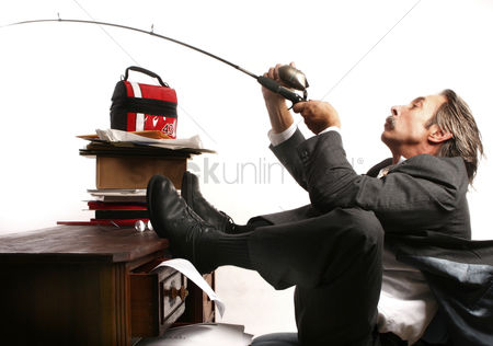Conceptual : Businessman fishing at his table