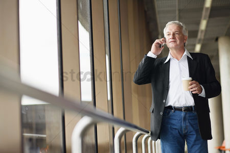 Food  beverage : Businessman holding a cup of coffee while talking on the phone