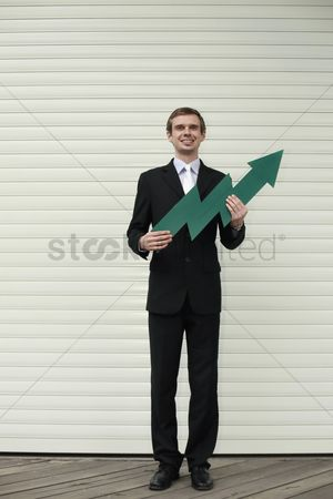 Cardboard cutout : Businessman holding an arrow pointing up