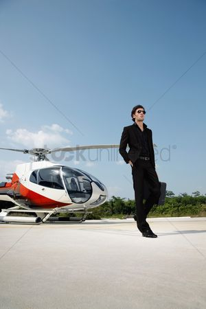 Pocket : Businessman holding briefcase with helicopter at helipad