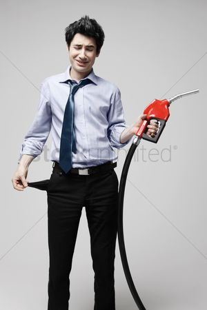Pocket : Businessman holding fuel pump and pulling out his empty pocket