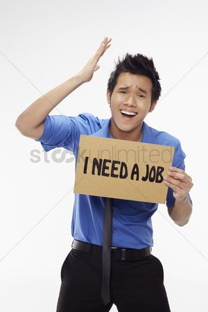 Unemployment : Businessman holding  i need a job  sign