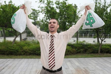 Business Finance : Businessman holding money bags