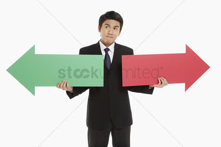 Masculinity : Businessman holding up a red and green arrow