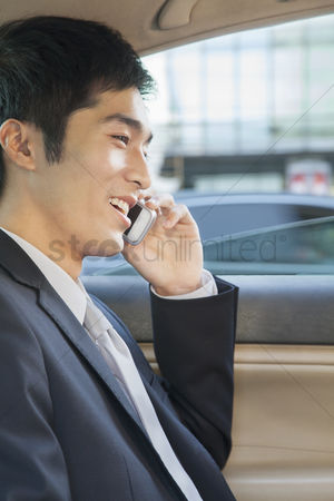 Interior : Businessman in back seat of car on the phone