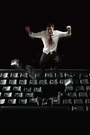 Technology background : Businessman jumping on computer keyboard