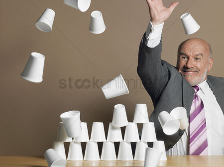 Bald : Businessman knocking down pyramid of plastic cups