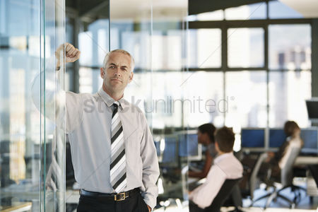 Pocket : Businessman leaning on door in office with office workers in background