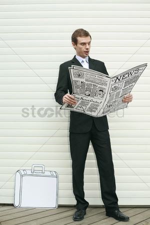 Cardboard cutout : Businessman looking shocked while reading newspaper