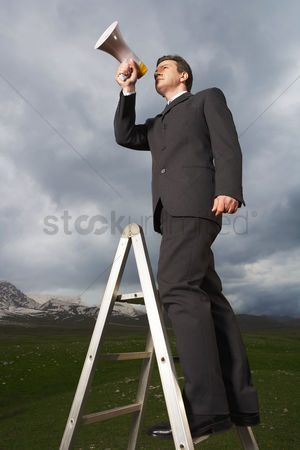 Moody : Businessman on ladder in mountain field speaking through megaphone low angle view