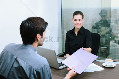 Face : Businessman passing document to businesswoman