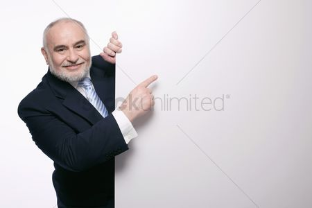 Business suit : Businessman pointing at placard