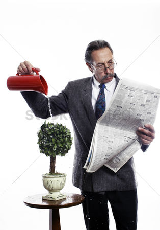 Business suit : Businessman reading newspaper while watering the plants