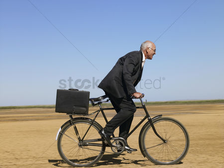 Land : Businessman riding bicycle in desert