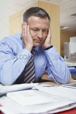 Pain : Businessman sitting at desk with head in hands